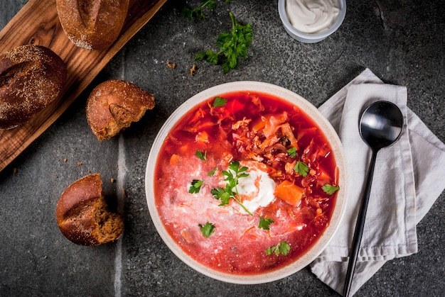 Borscht tradicional da sopa de vegetais do russo ucraniano, com creme duro. rolos de pão de centeio salsa, na mesa de pedra preta, vista superior do espaço cópia