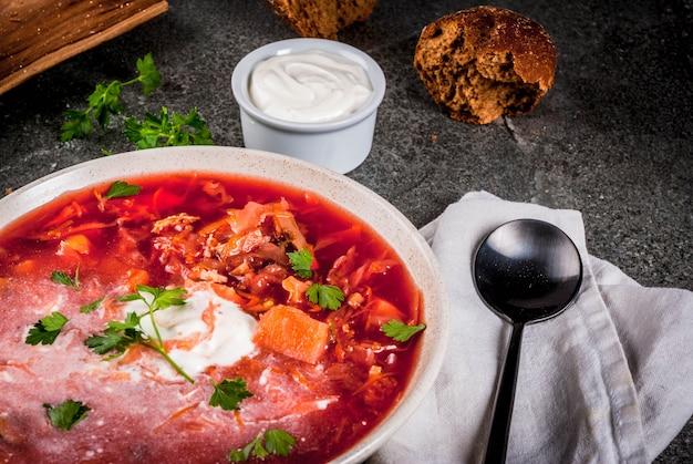 Borscht tradicional da sopa de vegetais do russo ucraniano, com creme duro. rolos de pão de centeio salsa,