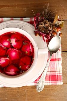 Borscht vermelho claro polonês tradicional com bolinhos na tigela na bandeja e na mesa de madeira