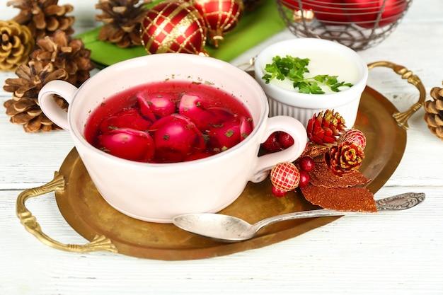Borscht vermelho transparente polonês tradicional com bolinhos e enfeites de natal em fundo de madeira