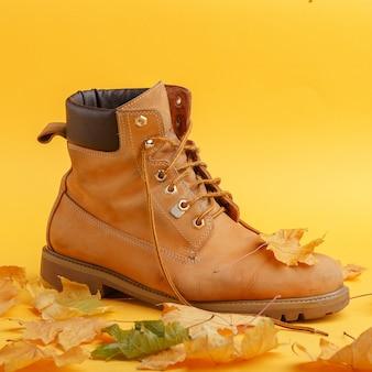 Bota amarela usada fica em folhas secas de outono