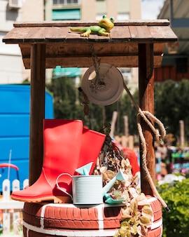 Bota de borracha vermelha; regador e pá sobre o poço artesanal no jardim