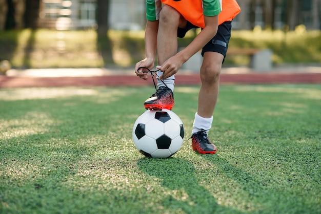 Bota de jogador de futebol amarrando o cadarço no estádio de futebol.