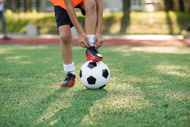Bota de jogador de futebol que coloca a perna na bola e amarrando o cadarço.