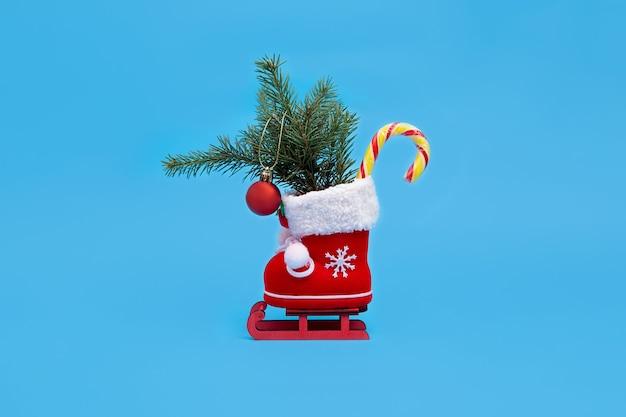 Bota de natal vermelha com pirulito de presentes e bola vermelha de natal em um trenó de natal