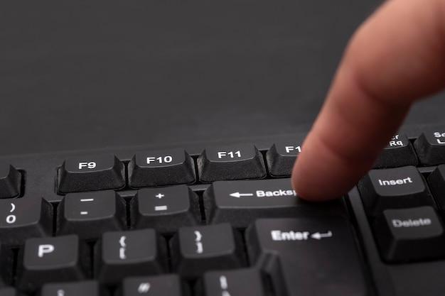 Botão backspace no teclado do computador. o dedo pressiona uma tecla de retrocesso. macro de teclado