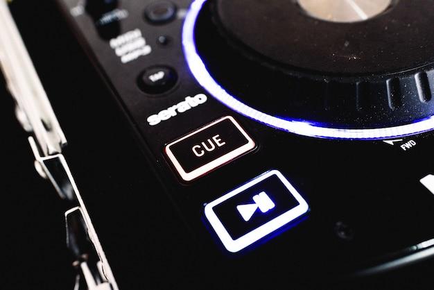 Botão cue and play em um mixer preto.
