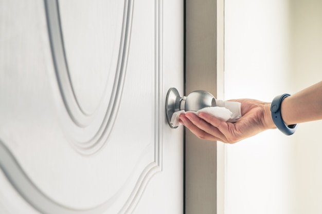 Botão da porta de limpeza com spray de álcool para prevenção do coronavírus covid-19