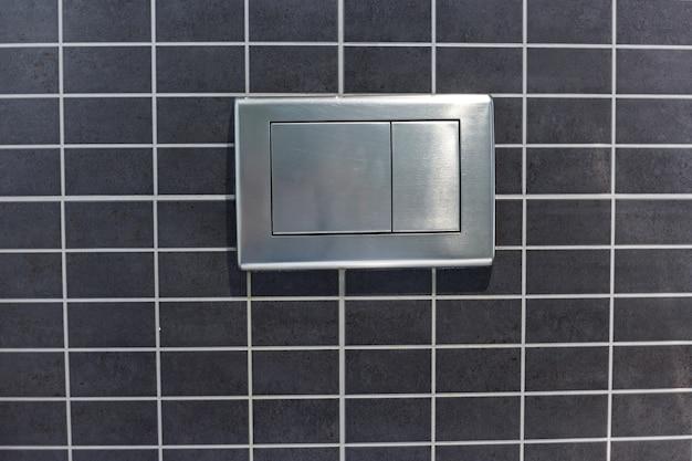 Botão de descarga metálico na parede do vaso sanitário.