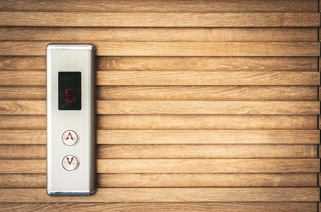 Botão de elevador closeup e led monitor no fundo de madeira com espaço de cópia