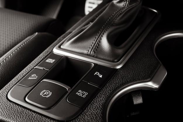 Botão de freio de mão eletrônico em um carro novo com detalhes luxuosos e modernos