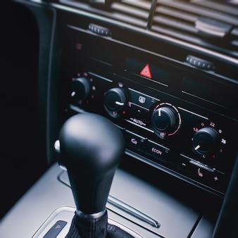 Botão de parada de emergência com sinal triangular vermelho e painel de controle de temperatura em detalhes modernos de interior de carro de luxo