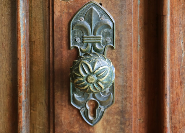 Botão de porta decorativa vintage na porta de madeira marrom, chachapoyas, norte do peru