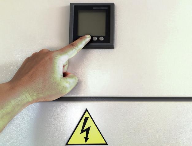 Botão de pressão da mão do engenheiro no interruptor ou disjuntor aberto uso do painel de controle da indústria elétrica