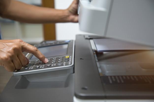 Botão de pressão de mão em close para usar a copiadora ou máquina xerox.