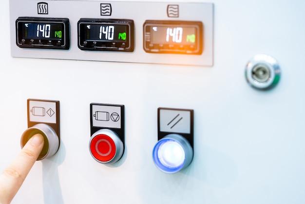 Botão de pressão verde de mão do engenheiro para abrir a máquina de controle de temperatura.