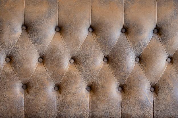 Botão de sofá de couro vintage para plano de fundo texturizado. fundo retrô texturizado.