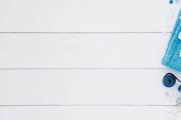 Botão; fita métrica; agulha e dedal na mesa branca com espaço para escrever o texto