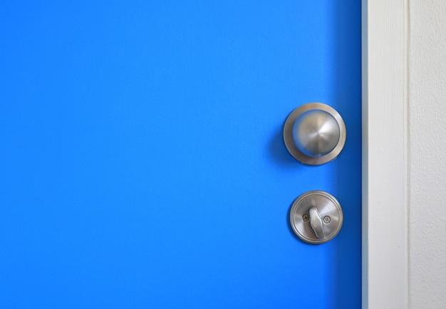 Botão inoxidável e trava do close-up na porta azul com espaço da cópia.