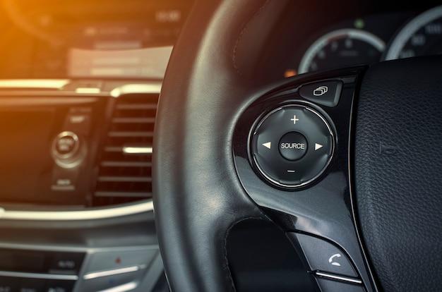 Botão multimídia no volante multifuncional em um carro de luxo.