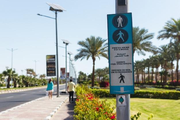 Botão para chamar a travessia de pedestres com a seta para cima. clique aqui para cruzá-lo escrito em quatro idiomas inglês, árabe, russo e alemão