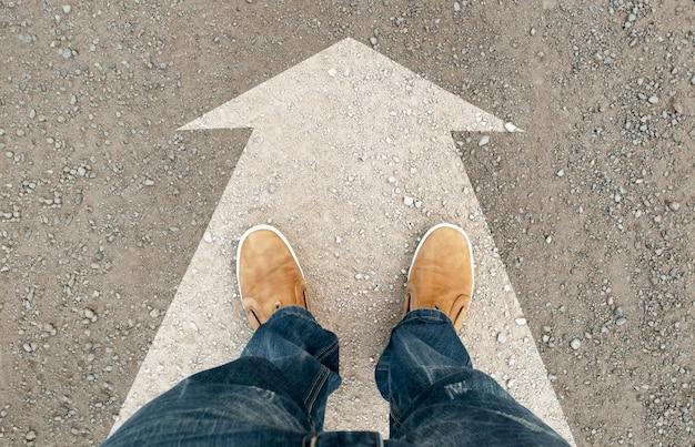 Botas amarelas na estrada com uma flecha