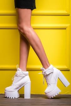 Botas brancas em uma plataforma alta e salto alto