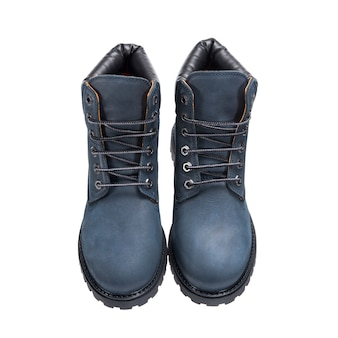 Botas cinza com cadarços no piso, sapatos de couro para o mau tempo isolados na superfície branca