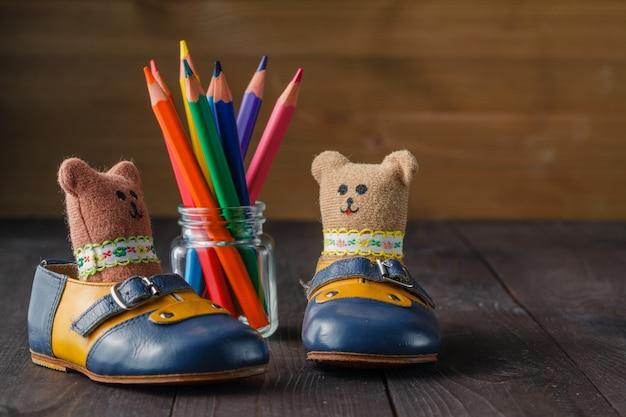 Botas de bebê e boneca de brinquedo na mesa de madeira