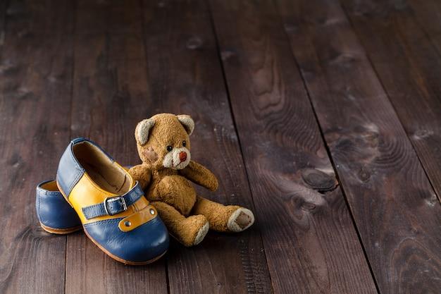 Botas de bebê na mesa de madeira sobre a superfície do grunge de parede, estilo vintage