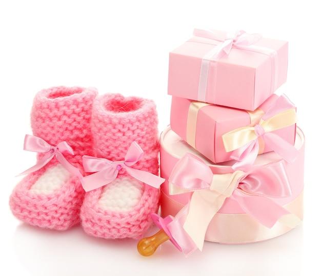 Botas de bebê rosa, chupeta e presentes isolados no branco