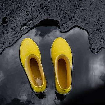 Botas de borracha amarelas estão em uma poça em que as nuvens são refletidas.