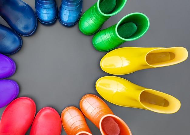 Botas de borracha colorido arco-íris na superfície cinza em um círculo. vista superior, espaço para texto.