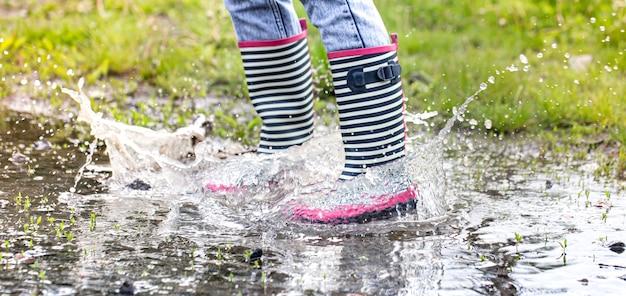 Botas de borracha em uma poça no processo de salto com respingos de água de perto.