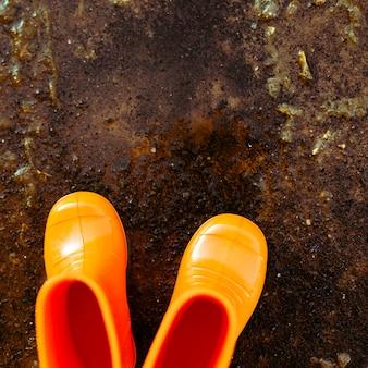 Botas de borracha laranja em pé ao lado da poça.