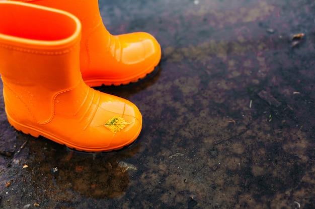 Botas de borracha laranja em pé em uma poça