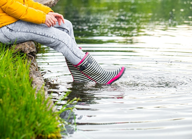 Botas de borracha listradas no rio com salpicos de água. conceito de primavera na aldeia.