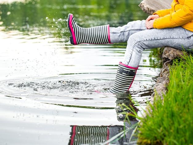 Botas de borracha listradas no rio com salpicos de água. primavera na aldeia.