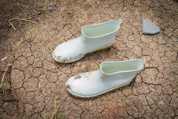 Botas de borracha sujas no chão na fazenda