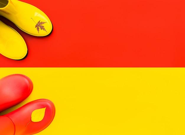 Botas de borracha vermelha para ficar em um fundo amarelo