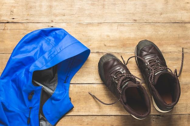 Botas de caminhada e jaqueta em um espaço de madeira. o conceito de caminhadas, turismo, acampamento, montanhas, floresta. bandeira. camada plana, vista superior