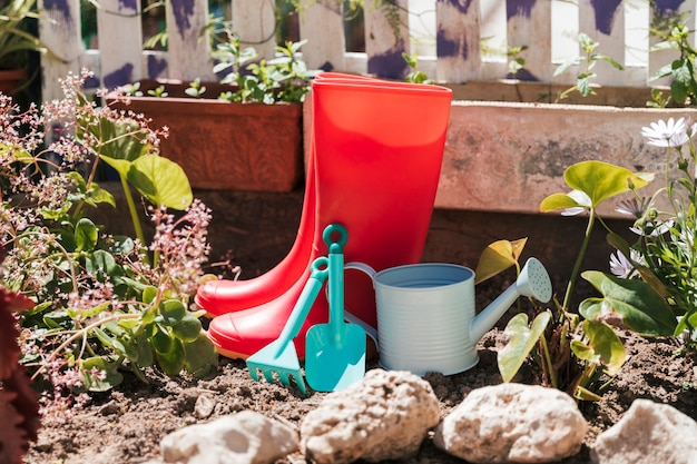 Botas de cano alto vermelhas; regador e ferramentas de jardinagem no jardim