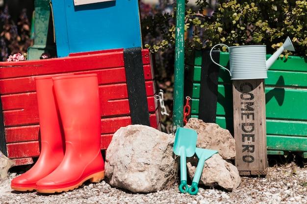 Botas de cano alto vermelhas; regador; ferramentas de jardinagem no jardim