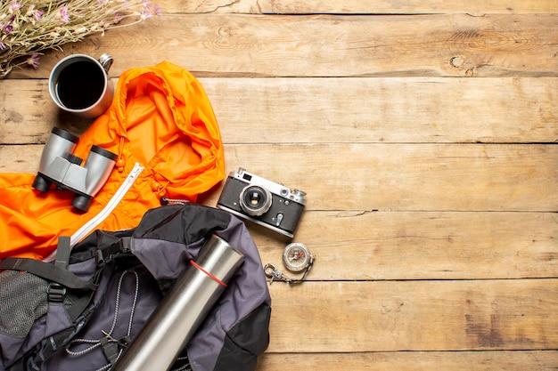 Botas de chuva amarela, mochila, binóculos, jaqueta, equipamento de campismo em um fundo de madeira. o conceito de caminhadas, turismo, acampamento, montanhas, floresta. bandeira. vista plana, vista superior