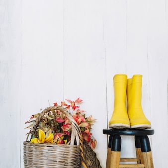 Botas de chuva perto de cestas com folhas secas