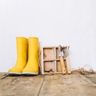 Botas de chuva perto de ferramentas de caixa e jardinagem