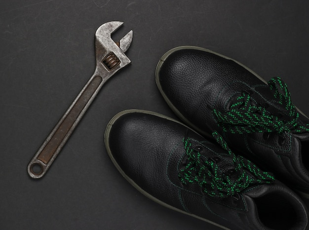 Botas de couro e chave ajustável em fundo preto