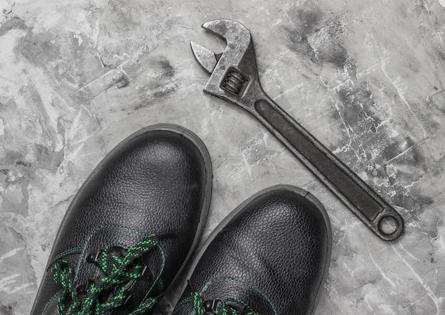 Botas de couro e chave inglesa em fundo cinza de concreto. vista do topo