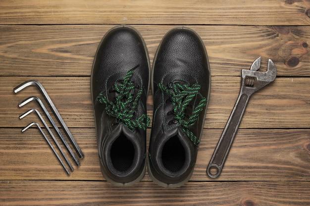 Botas de couro e conjunto de chave em fundo de madeira. vista do topo