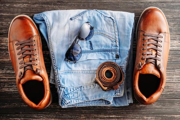 Botas de couro marrom, cinto, óculos de sol e jeans azul